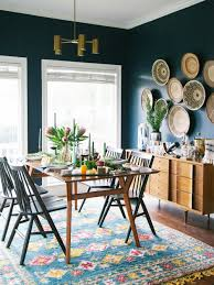 this dining room feels both moody and bright thanks to the rich blue walls and bright kilim the contemporary windsor chairs add modern flair