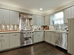 gray kitchen with tongue and groove front cabinets accented with nickel cabinet pulls alongside gray granite counters with a stainless steel backsplash