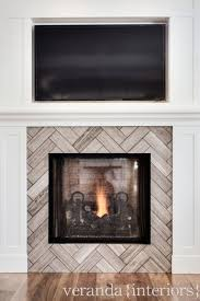 gorgeous fireplace with batten and board trim and recessed flat screen tv the fireplace surround is tiled with a stone tile laid in a herringbone pattern