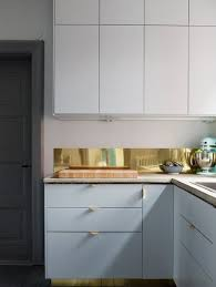 brass sheet kitchen backsplash and matching drawer handles for a chic and  glam look