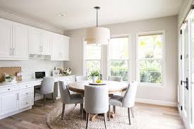 gorgeous breakfast room boasts a 2 tier round linen shade pendant hung over a round wood dining table positioned on a round jute rug surrounded by