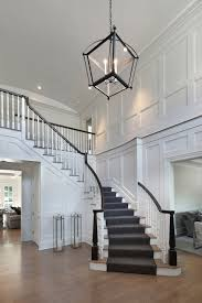 two story foyer features restoration warehouse hollis pendant illuminating board and batten walls alongside a sweeping staircase lined with gray stair