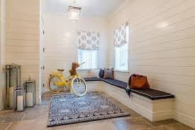 a cornice lantern hangs from a pale blue ceiling over a blue medallion rug placed in a beautifully styled mudroom featuring a white built in l shaped topped