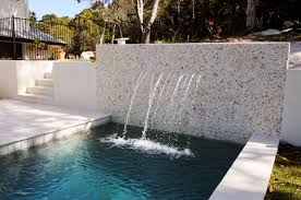 A stone and mortar wall at the edge of one pool with several fountains  streaming from