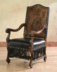 custom made dining room arm chair with cowhide and leather coverings and tel skirt with carved wood for legs and arms