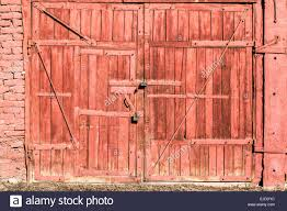 a red painted old wooden garage door with locks
