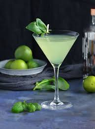 a martini glass filled with a green colored basil vodka gimlet and garnished with basil leaves