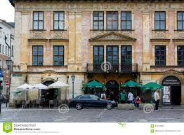 Krakow poland may 25 2017 historic building at the small market square on the ground floor are two outdoor restaurants there is a parked car and
