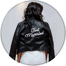 bride wearing a black leather jacket with just married embroidered in white