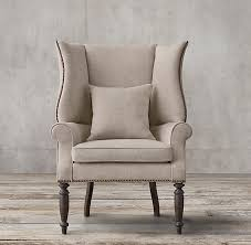 contemporary take on a english wingback chair combines the original s high back and sheltering wings with padded scroll arms and brass nailhead trim for