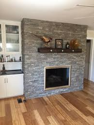 An outdated brick fireplace covered in stacked stone style panels made it  look brand new.