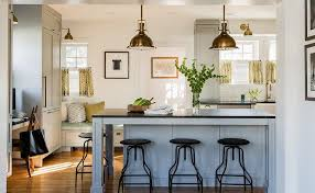 gorgeous kitchen features a pair of restoration hardware harmon pendants in antique brass illuminating a gray kitchen island topped with soapstone lined