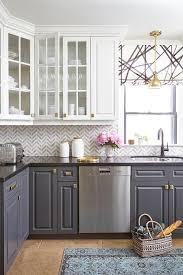 glass front upper cabinets and gray lower cabinets with marble chevron tiles