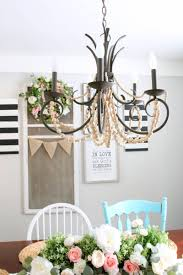 i ve been eyeing some gorgeous wood bead chandeliers for a while now i had been going around and around in my mind about whether i wanted to switch out my