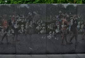 visitors to the korean war memorial pass a wall etched with candid photos of g i s from