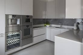 above the large format tile flooring we see sleek white countertops and a grey marble backsplash offering contrast and texture