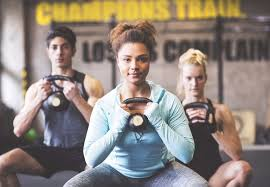 confident young woman with partners lifting kettlebell in gym