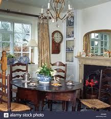 rush seated ladder back chairs and antique oak table in front of fireplace in cote dining room with wall clock beside window