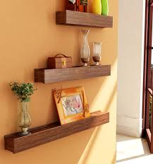 living room decoration with three section wall shelves made of wooden in brown finished attached on