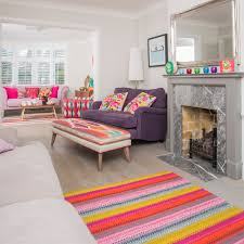 Use family friendly flooring. Large bright living room with colourful rugs  and sofas