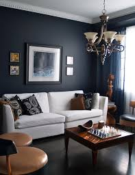masculine space with a dark navy accent wall tan chairs warm wood furniture and