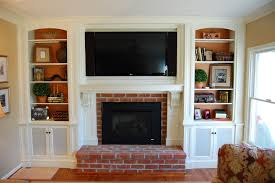 brown brick fireplace plus white mantel and large tv above on the middle of white wooden