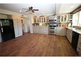 cream painted raised panel maple l shaped conventional horseshoe kitchen cabinets brown distressed wood laminate flooring black pantry storage dishwasher