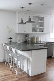 White cabinets, gray counters, wood floors Breakfast bar island don't like  the open cabinet but this layout fits the kitchen currently