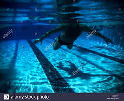 swimmer silhouette and shadow below on swimming pool floor reflections ripples lane marker