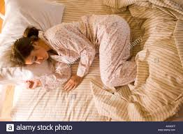 Woman sleeping in the fetal position in her pajamas in bed