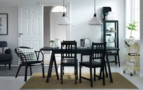 A dining room with a black dining table and chairs. Combined with a beige  trolley