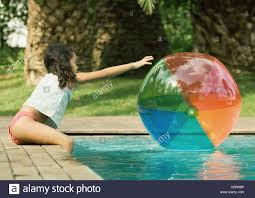 pool water with beach ball. Girl Sitting On Edge Of Pool, Reaching For Beach Ball In Water Pool With O