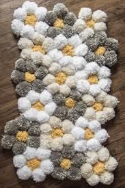 a pom pom rug designed with daisy shapes in whites creams and greys with bright