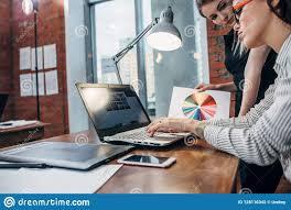 Interior Designer Laptop Female Interior Designer Working With A Customer Watching