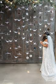 a bride stands in front of paper cranes and planet cutouts hanging vertically in front of