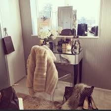 chic walk in closet features a mirrored makeup vanity and ghost chair placed under a window ledge lined with designer ping bags