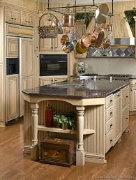 distressed antique white cabinets. country style with distressed antique white kitchen cabinets black granite countertop and island adorned hanging pans