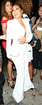 Adrienne Bailon goes braless in white two piece suit on LA night.