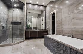Modern master bathroom with gray limestone walls and rainfall shower