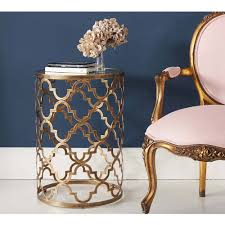 brass and glass chic side table with a quatrefoil design
