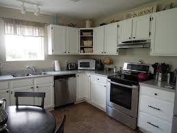 marvelous l shaped white cabinets with black rounded breakfast table set also grey wall painted in small kitchen designs