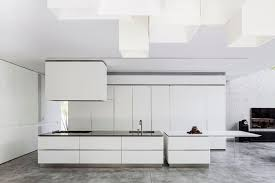 the use of white cabinets and concrete floors give this kitchen a modern and industrial look