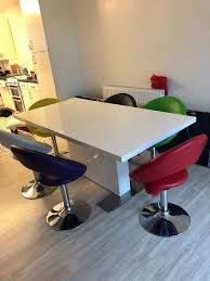 white gloss dining table and 6 multi coloured chairs