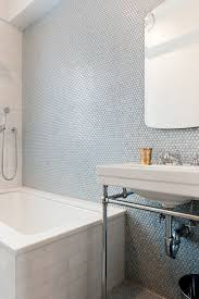 penny tiles in blue shades done right with subway tiles on the bathtub