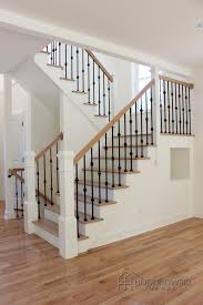 Light wood floor, treads and rail, white risers, iron spindles, white newel  posts.