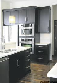 Dark Expresso Cabinets Topped With White Quartz Countertops Create