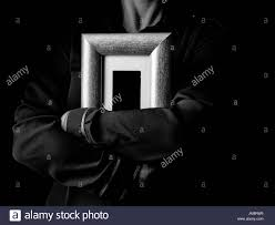 black mania female hands isolated on black hugging a photo frame