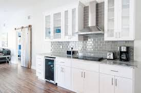 small one wall kitchen with white cabinets and gray subway tile backsplash