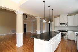 farmhouse style kitchen with white cabinets black granite counter tops island white farm sink white wainscot columns brick tile backsplash