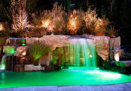this natural waterfall protects a peaceful fake rock grotto along one side of the custom swimming pool artificial rock mimics one of nature s unique
